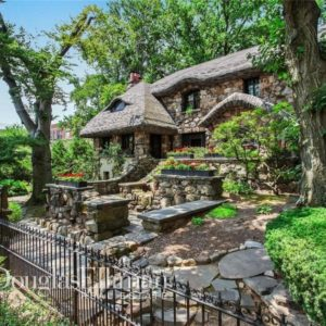 This is the exterior of this house with stone walls that pair well with the surrounding landscape bordered with wrought-iron fences. Image courtesy of Toptenrealestatedeals.com.