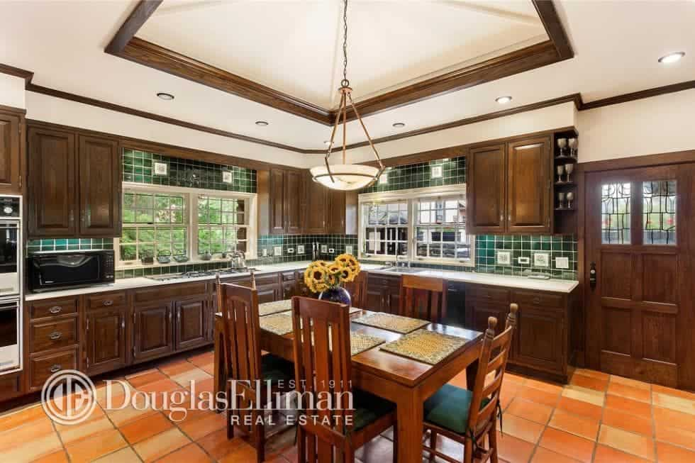This kitchen has dark wooden cabinetry to match the informal dining area's wooden table in the middle of the kitchen topped with a tray ceiling. Image courtesy of Toptenrealestatedeals.com.