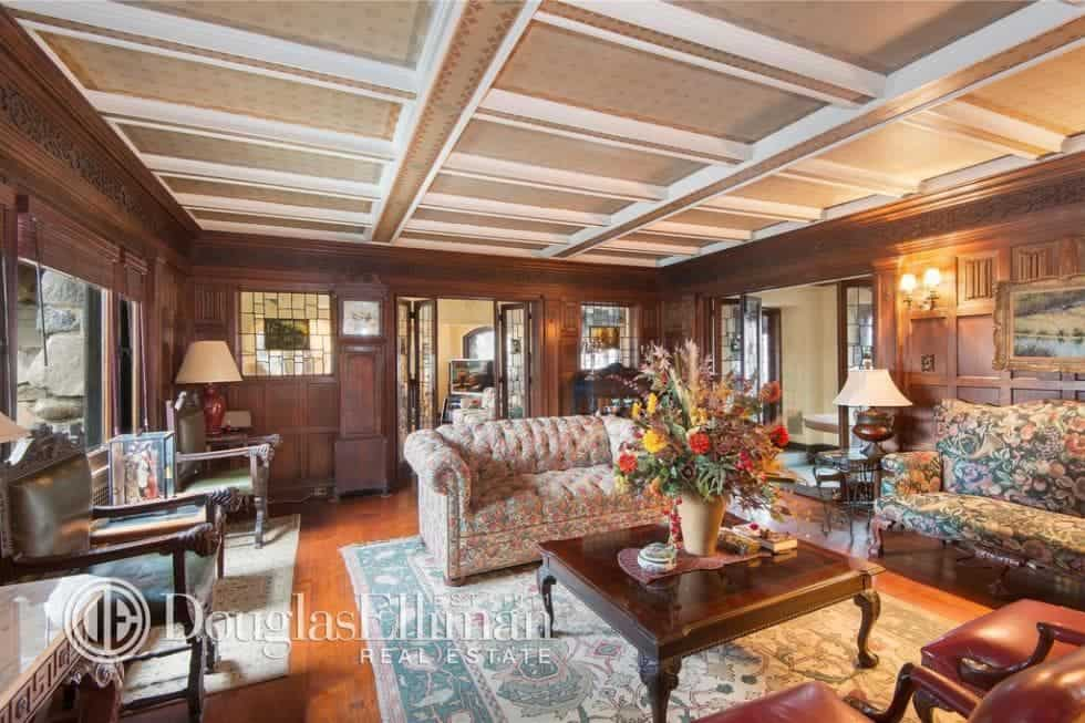 This is the spacious living room with a dark wooden coffee table that matches well with the wood paneling of the walls. These are topped with a coffered beige ceiling that pairs well with the tufted sofa. Image courtesy of Toptenrealestatedeals.com.