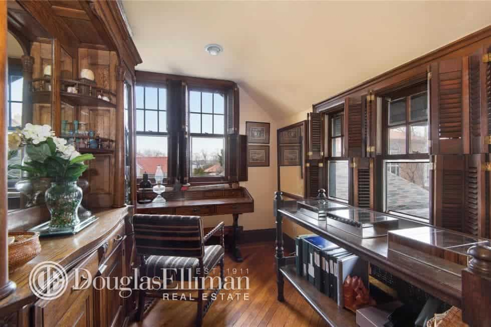 This is the home office with various wooden structures that pair well with the dark wooden desk and chair. These are then complemented by the beige ceiling and natural lights coming in from the large window. Image courtesy of Toptenrealestatedeals.com.
