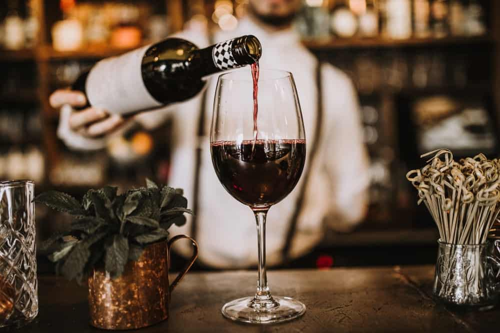 Bartender pouring red wine from a bottle in a wine glass.