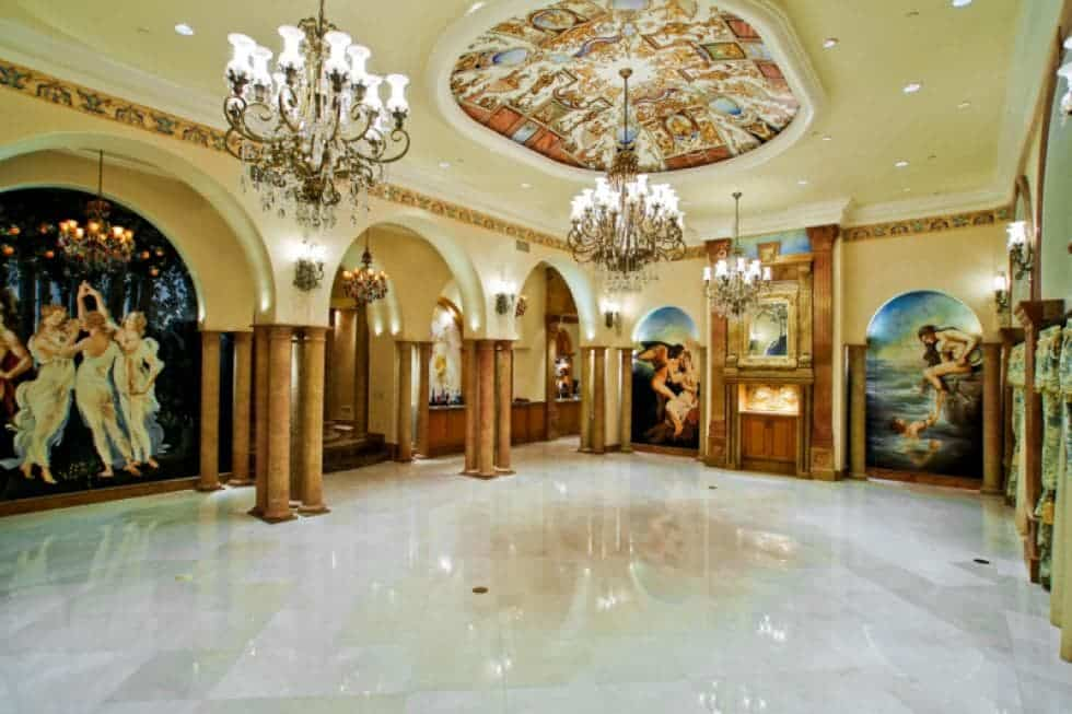 This is the grand ballroom with a colorful dome ceiling that hangs three large chandeliers that pair well with the sconces in between arches. Image courtesy of Toptenrealestatedeals.com.