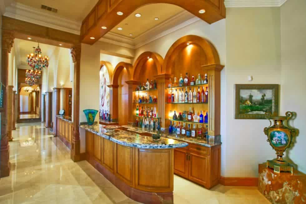 This is a look at the bar with wooden shelves and cabinets embedded into the wall along with arches across from the counter. Image courtesy of Toptenrealestatedeals.com.