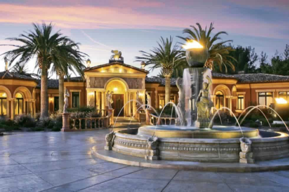 This is a view of the front of the mansion with a large fountain at the courtyard. You can also see here the warm exterior lighting of the house complemented by tall tropical trees. Image courtesy of Toptenrealestatedeals.com.