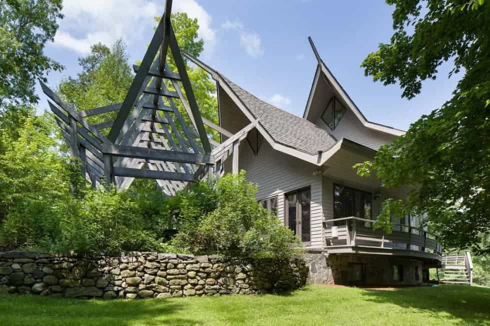 This is a view of the back of the house that has a unique tall A-frame roof design paired with shiplap exterior walls and lush landscaping of grass, trees and shrubs.