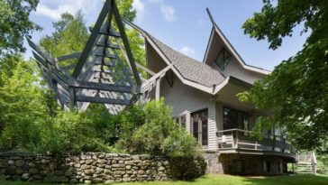 This is a look at the exterior of the house that has winged roofs and wooden deck balconies that are complemented by the surrounding lush landscape of tall trees and grass lawns. Image courtesy of Toptenrealestatedeals.com.