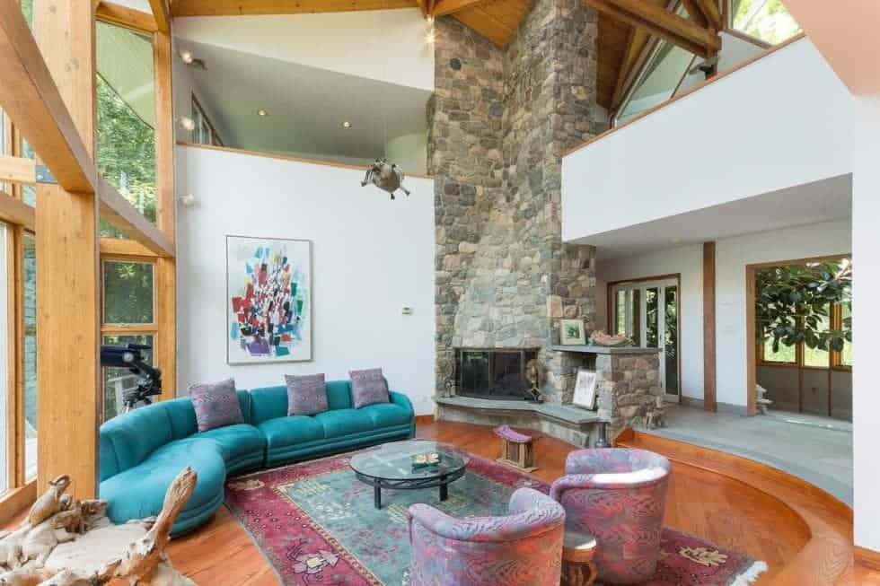 This is the spacious and airy living room that has a tall ceiling complemented by the tall stone structure of the fireplace across from the curved sectional sofa and its round coffee table on a colorful area rug. Image courtesy of Toptenrealestatedeals.com.