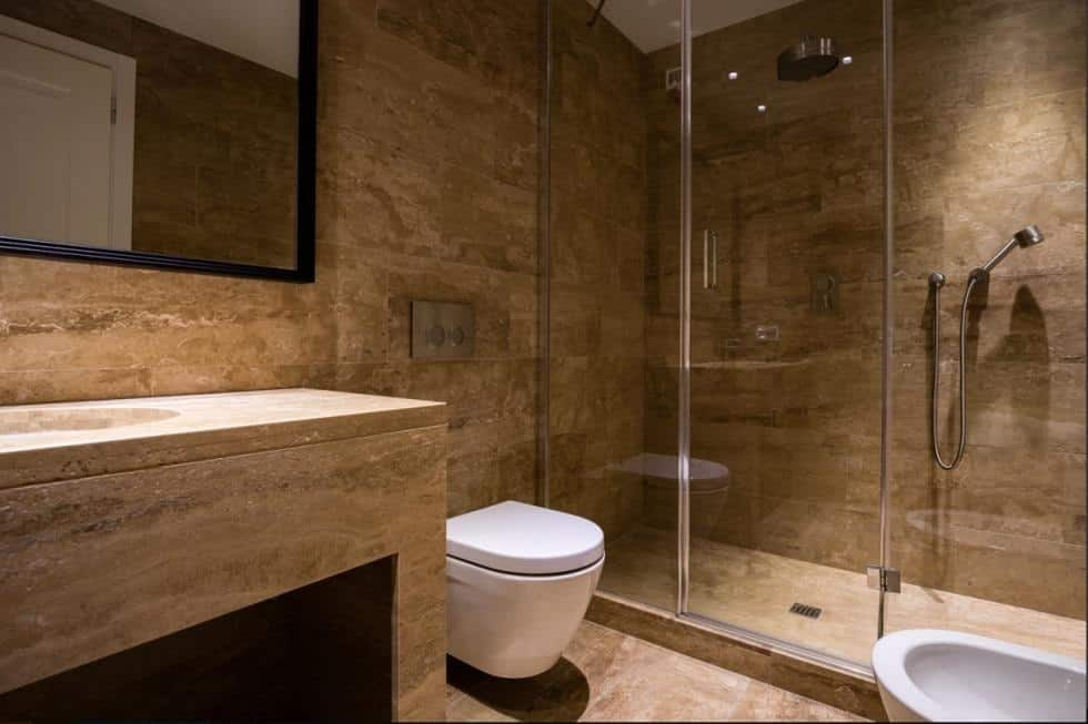 This is the bathroom with consistent brown marble on its floor, walls and the vanity. You can also see here the glass-enclosed shower area on the far side. Image courtesy of Toptenrealestatedeals.com.