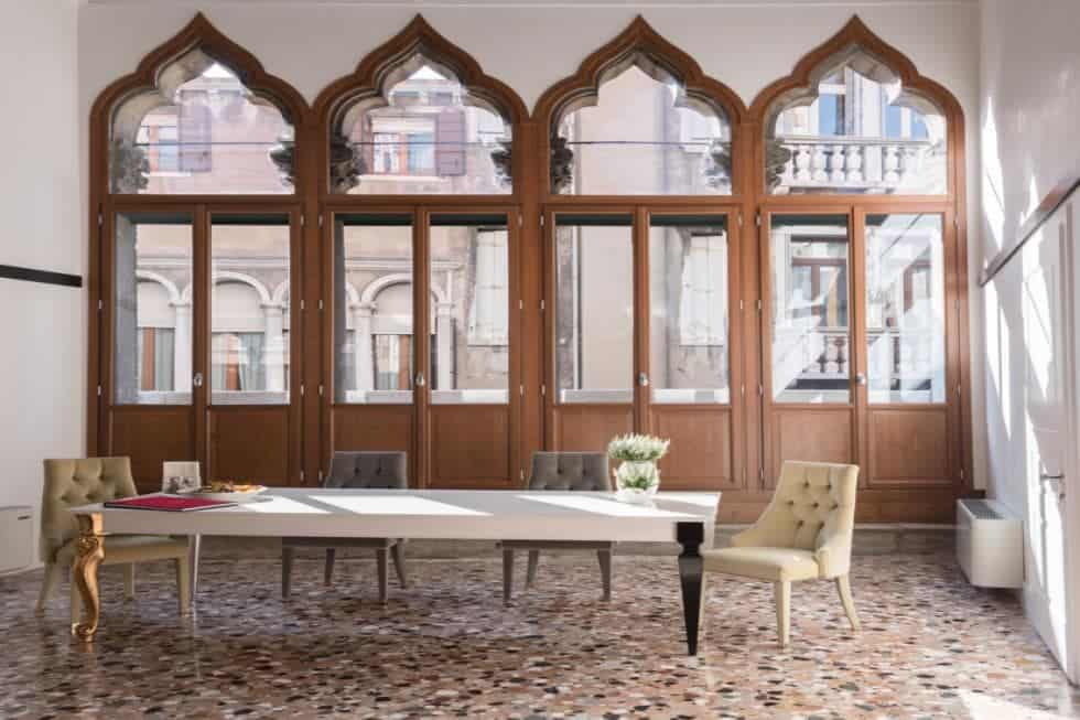 This is the spacious dining room that has a long dining table and tall ceiling. These are then complemented by the row of tall arched windows with wooden frames. Image courtesy of Toptenrealestatedeals.com.