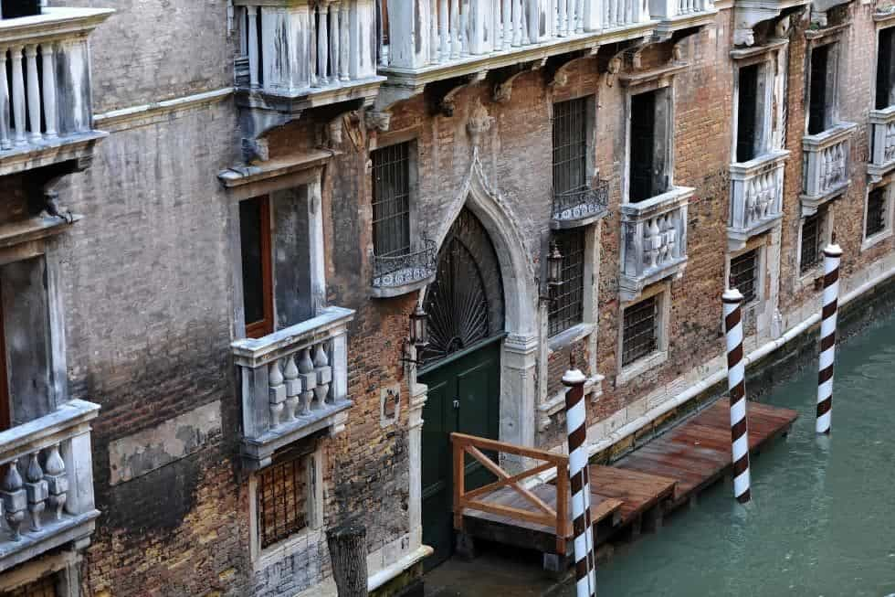 This is a closer look at the main entrance of the building with a large arched main door surrounded by red brick exterior walls and a wooden walkway from its private boat dock. Image courtesy of Toptenrealestatedeals.com.