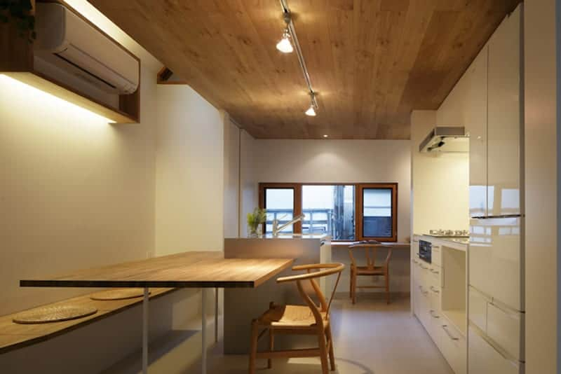 The eat-in kitchen is topped with a wooden ceiling that supports modern lighting and spotlights that illuminated the kitchen along with the window on the far side.