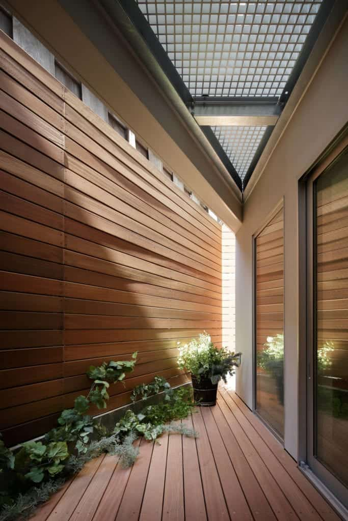 The wooden walls and floor of the entrance is complemented by the row of plants on the side lining the wall with a potted plant at the far corner.