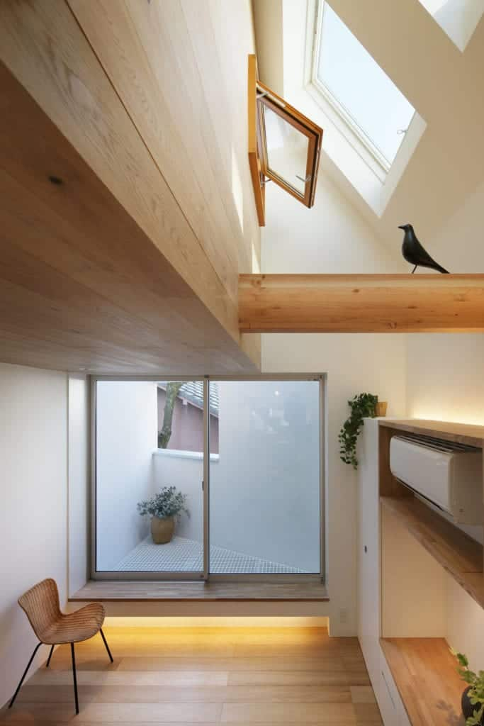 This is a look at the upper level of the house with skylights that bring in natural lighting for the white walls and wooden elements.