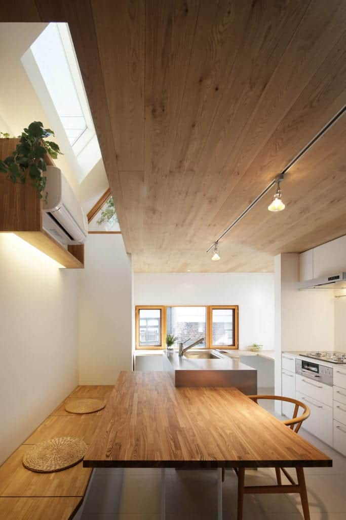 Above the built-in wooden bench of the kitchen is a floating wooden shelf that houses the split-type air conditioner.