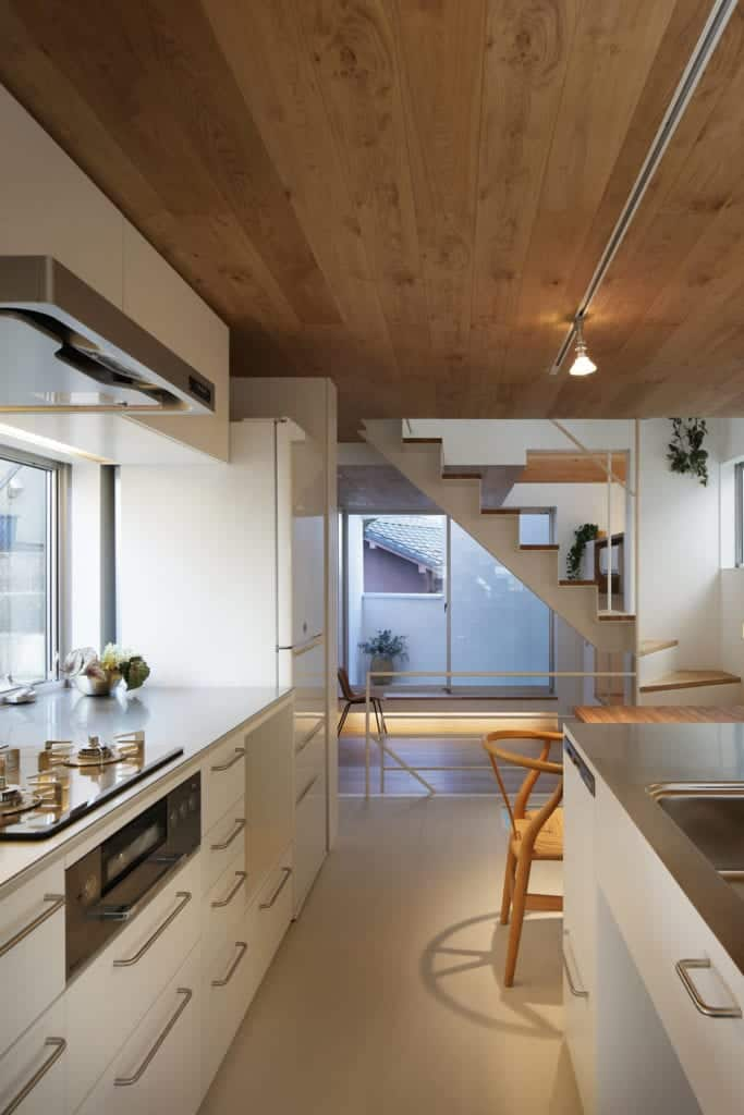 Across from the built-in wooden dining table of the kitchen is the cooking area surrounded by white cabinetry and a modern vent above.