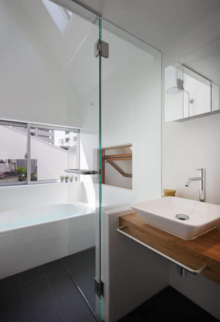 The modern bathroom has a bathtub and a floating sink that is separated with a half-wall of glass.
