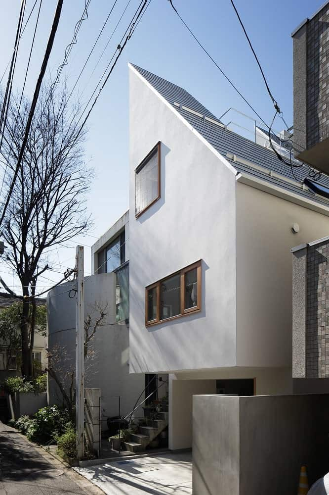 This angled view of the front of the house showcases the unique shape of the house along with its roof.