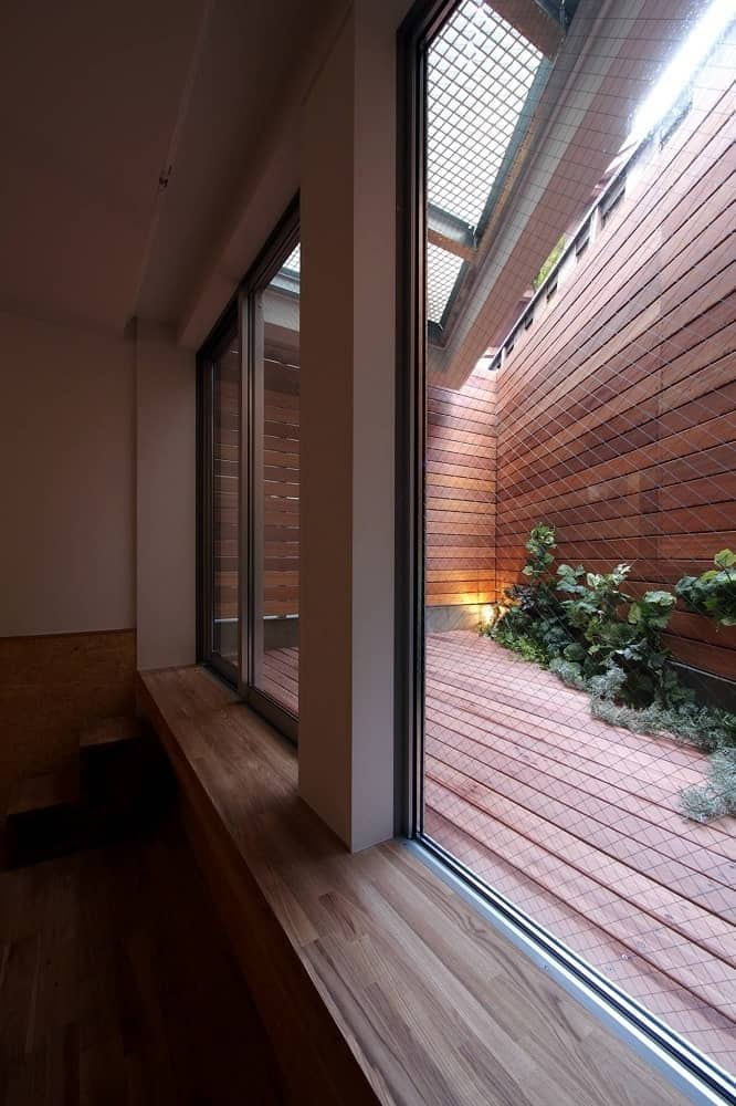 After climbing the stairs on the side of the car port, you come to this entrance with a wooden deck floor to match the walls topped with skylights.