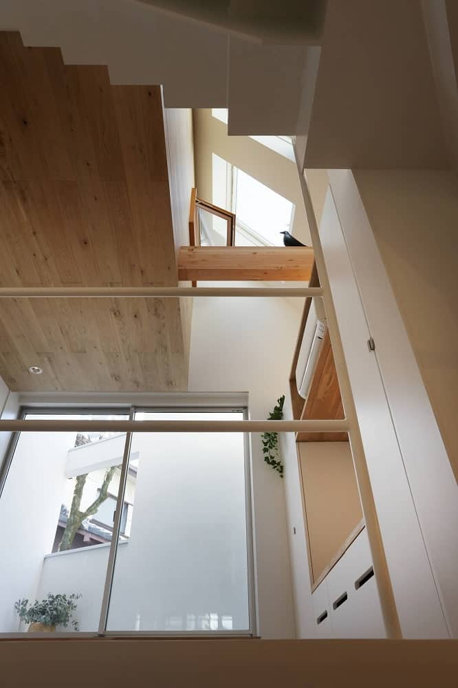 This is a look at the tall three-level ceiling of this part of the house with wooden ceilings and wooden beams adorned by a decorative figurine of a bird.