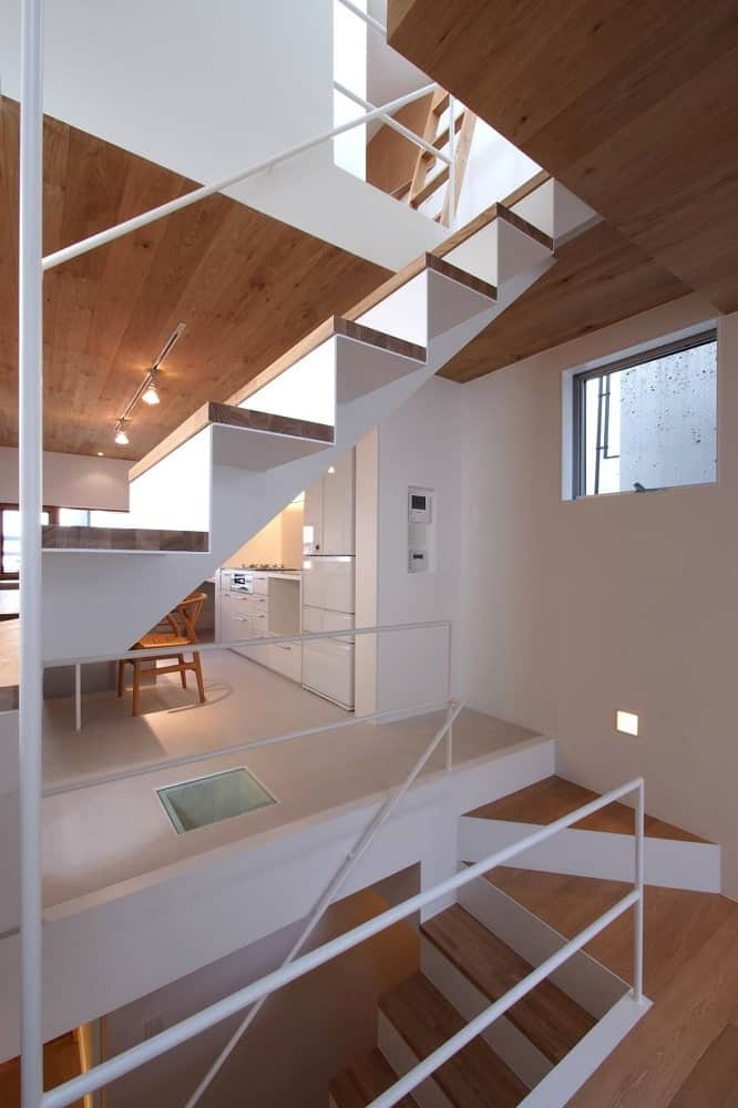 The wooden steps of the staircase match the wooden ceiling white the white walls match the white railings.