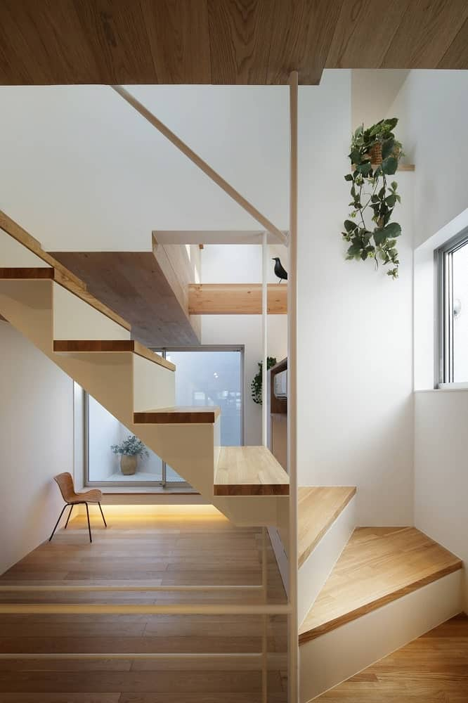 This closer look at the wooden staircase shows more of the wooden steps and bright walls adorned with hanging plants.