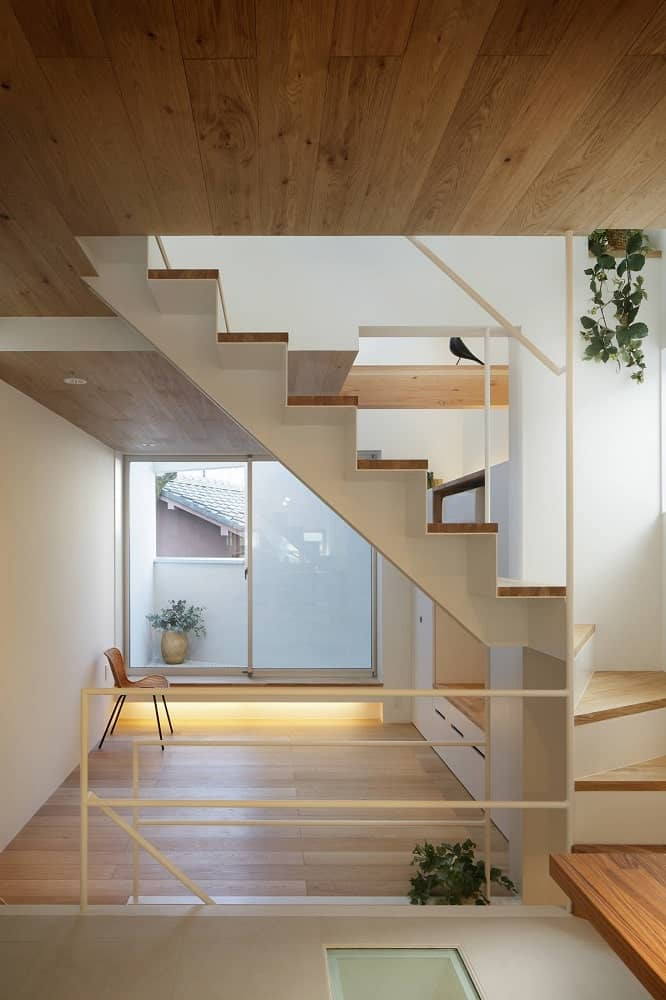 This is a look at the second floor landing with a hardwood flooring that complements the white walls and railings.
