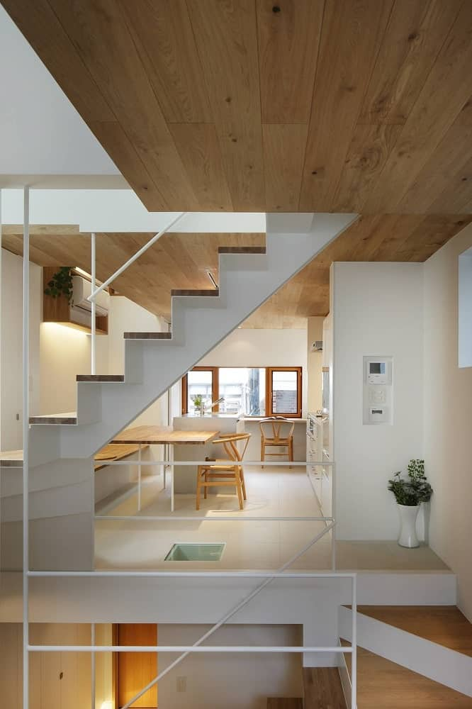 At the far side after the staircase, you can see the kitchen with a built-in wooden dining table on its kitchen island.