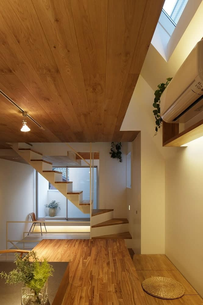 This is a look at the stairs and ceiling from the vantage of the built-in wooden table at the kitchen with matching tones.