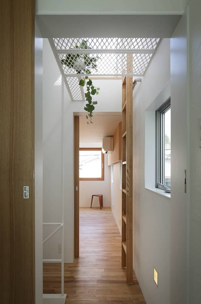 This is the hallway to the bathroom on the far side. The hallway has a wooden ladder that leads to the upper level.