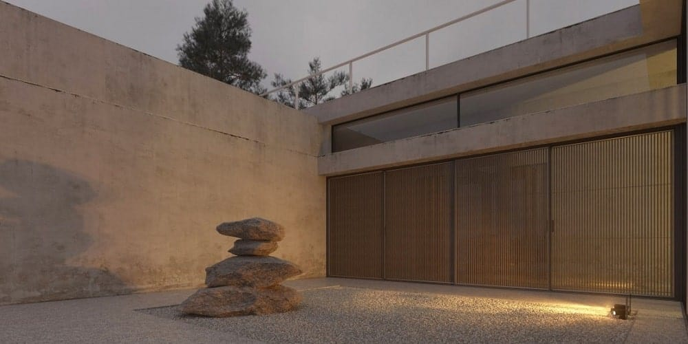 This isde of the house has a set of wooden sliding doors adorned with a landscaped setup of large decorative rocks and a graveled lawn lit by exterior lights.