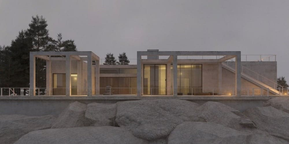 This view of the house shows the large rocks that support the fountation of the house that has a light beige exterior augmented by the warm outdoor lights.