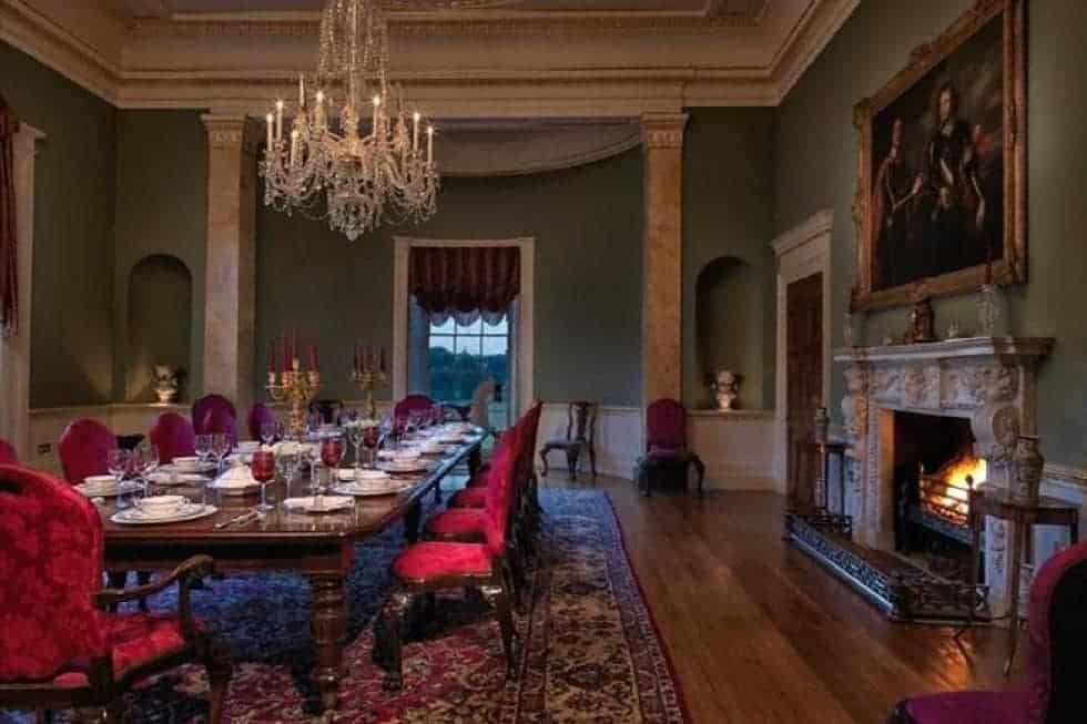 The formal dining room has a large dining table surrounded by cushioned chairs and warmed by the large fireplace on the side. Image courtesy of Toptenrealestatedeals.com.