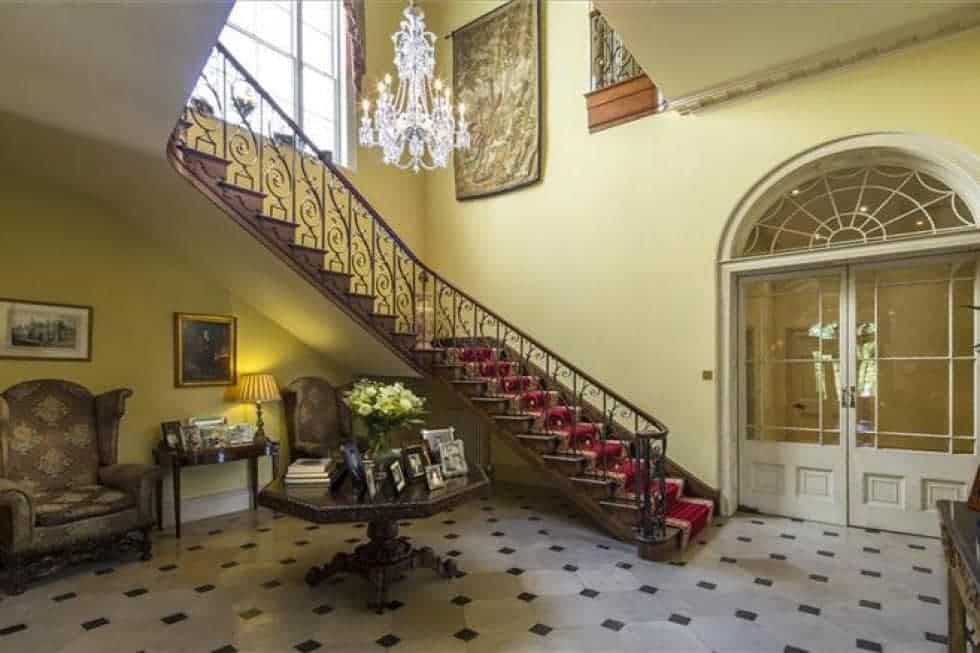 Upon entry of the main manor, you are welcomed by this elegant foyer with a curved staircase, a round wooden table and a crystal chandelier complemented by the beige walls. Image courtesy of Toptenrealestatedeals.com.