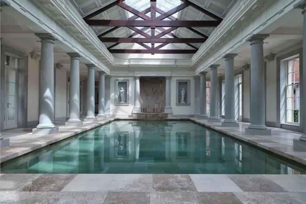 This is the massive indoor swimming pool of the estate with a tall cathedral beamed ceiling with skylights and surrounding Greek-style columns. Image courtesy of Toptenrealestatedeals.com.