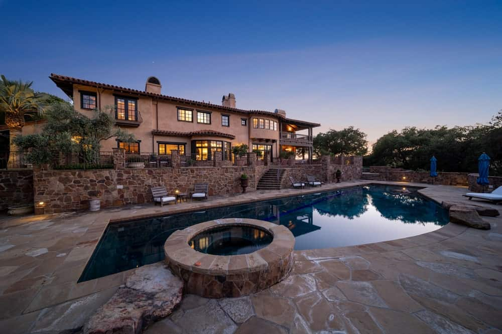 This is a view of the house from the vantage of the pool area. You can see here the earthy tones of the exterior walls that match the stone mosaic walkways around the pool and the warm glow of the windows.