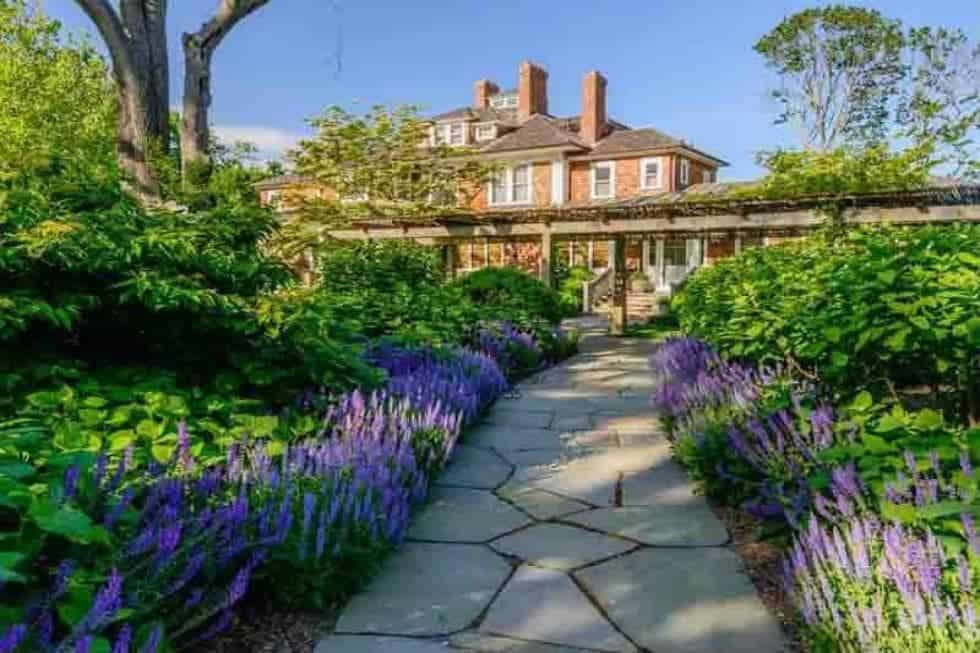 This is a front view of the main house with tall brick chimneys to match the exterior walls that are complemented by the landscaping that has mosaic stone walkways, flowering shrubs and tall trees. Image courtesy of Toptenrealestatedeals.com.