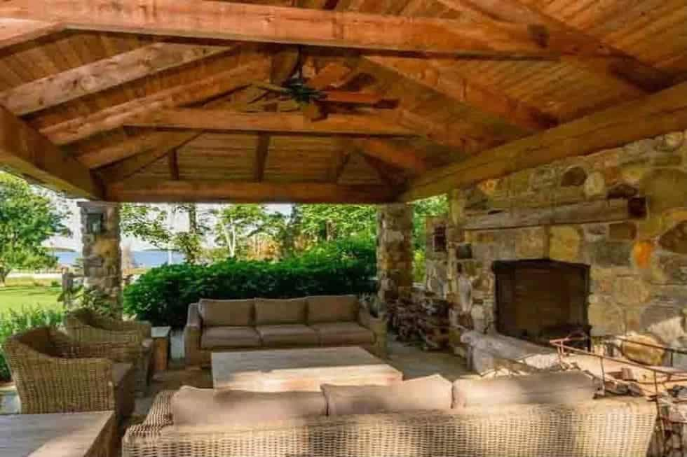 This is the covered patio with a large stone fireplace to pair with the beamed ceiling and outdoor sofas. Image courtesy of Toptenrealestatedeals.com.