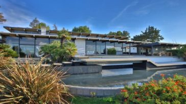 This is a view of the back of the house showcasing the glass and beam structure of the house exteriors adorned with water features and colorful shrubbery. Image courtesy of Toptenrealestatedeals.com.
