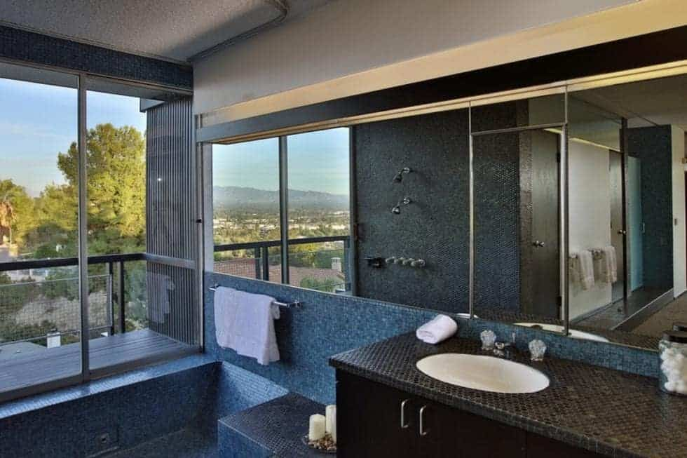 The glass window above the bathtub matches perfectly with the row of large mirrors that start from the vanity area to the bathtub area on the far side. Image courtesy of Toptenrealestatedeals.com.
