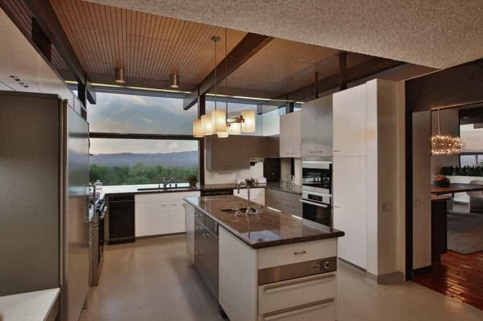 The kitchen has a dark tone to the countertops of the kitchen island and the surrounding cabinetry. These pair well with the stainless steel appliances as well the beams of the ceiling. Image courtesy of Toptenrealestatedeals.com.