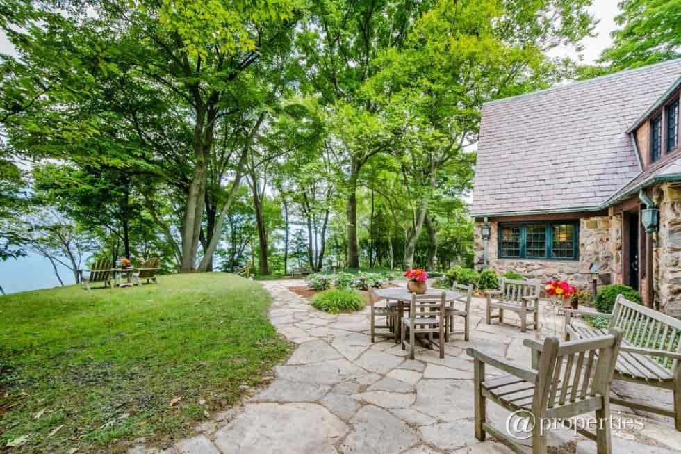 This is the back of the house that has a mosaic stone flooring and walkway adorned with the surrounding grass lawn and tall trees that serves as a background for the outdoor patio. Image courtesy of Toptenrealestatedeals.com.