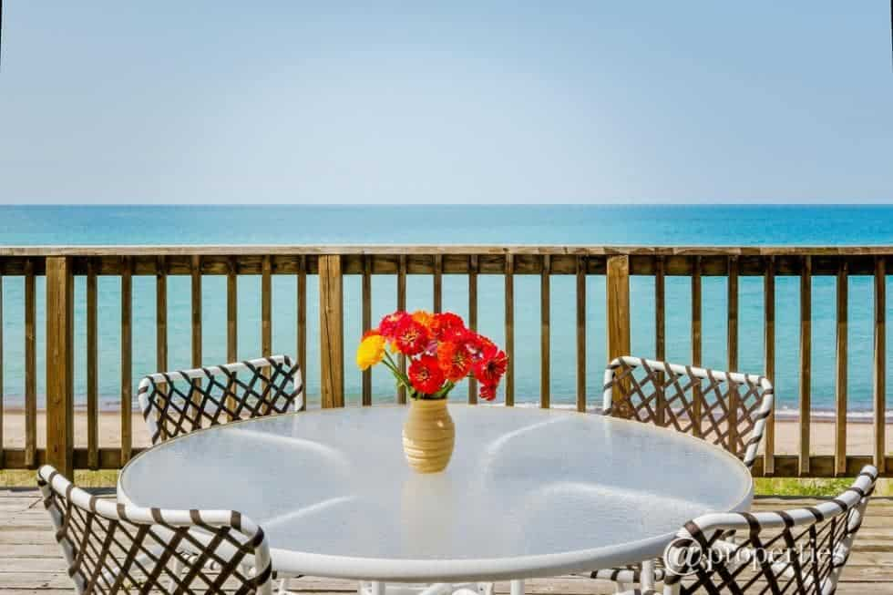 This is the deck terrace of the beachfront beach house that is fitted with a round outdoor dining area. Image courtesy of Toptenrealestatedeals.com.