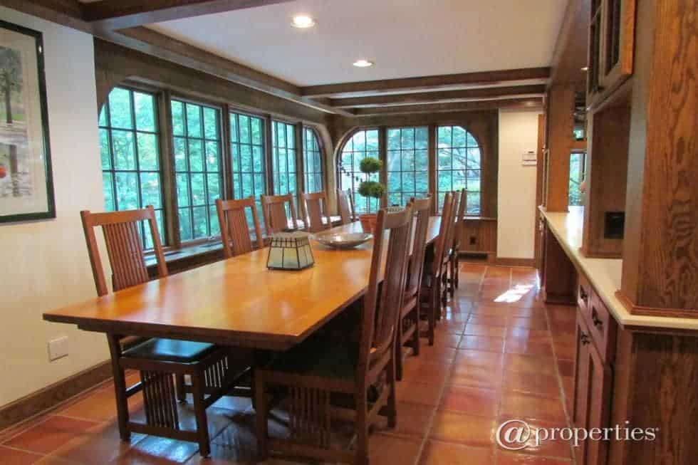 The dining room has a long rectangular wooden dining table surrounded by matching wooden chairs that match the large cebinetry as well as the frames of the windows that bring in natural lighting for the terracotta flooring tiles. Image courtesy of Toptenrealestatedeals.com.