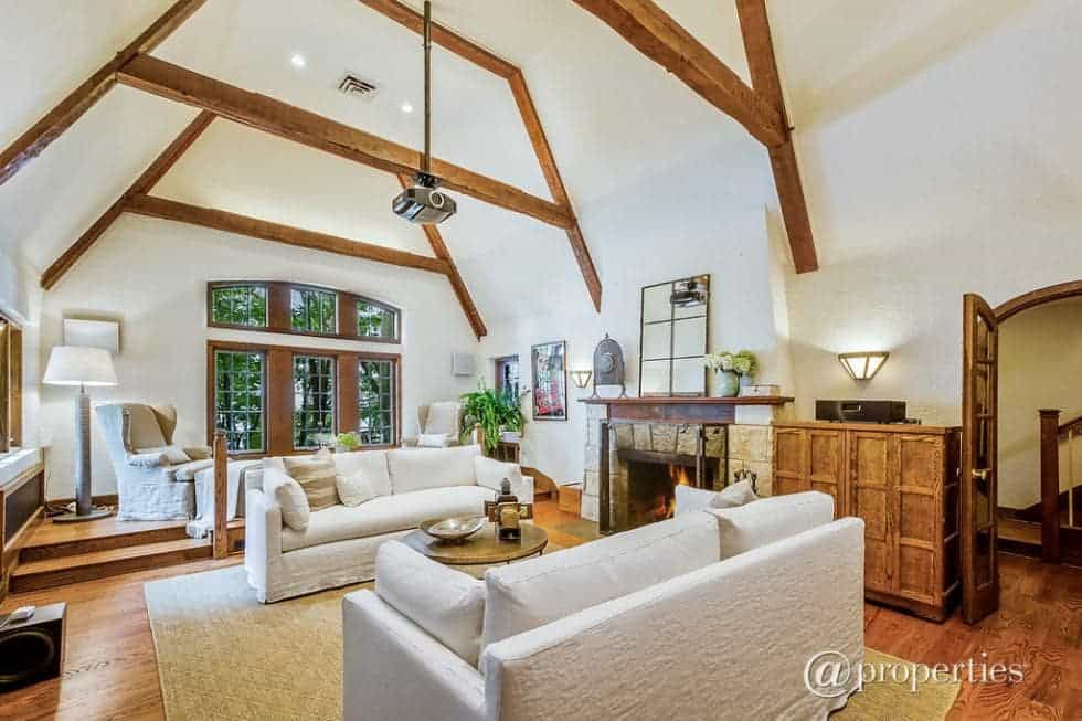 This bright and airy living room has a tall cove ceiling with exposed beams that match the hardwood flooring, cabinetry and the mantle of the fireplace across from the two sofas. Image courtesy of Toptenrealestatedeals.com.