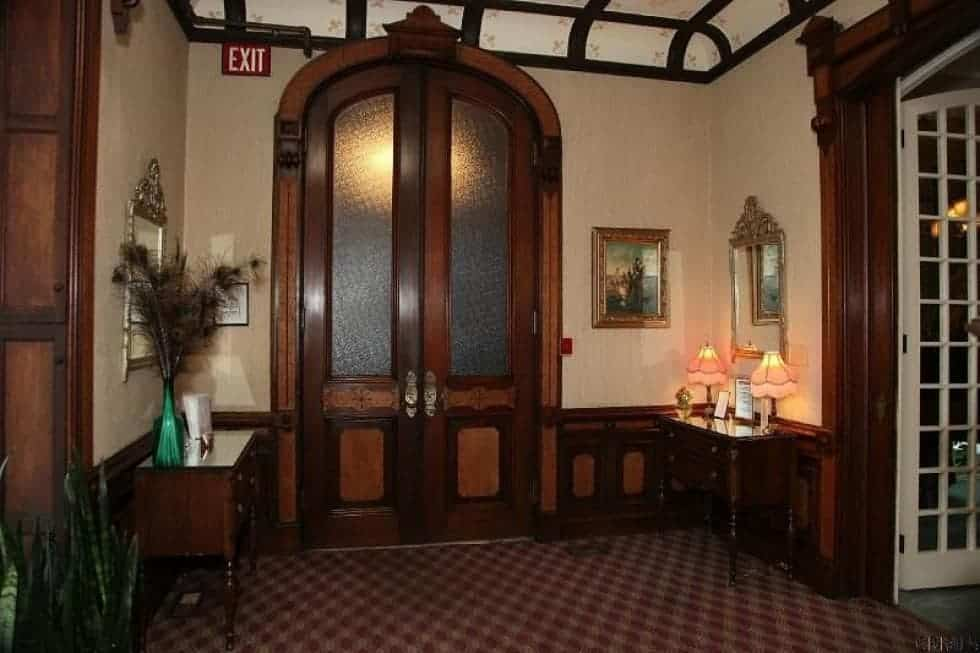 Upon entry of the house, you are welcomed by this foyer that has a dark wooden arched main door with glass panels. The frame of this blends well with the moldings and the console table. Image courtesy of Toptenrealestatedeals.com.