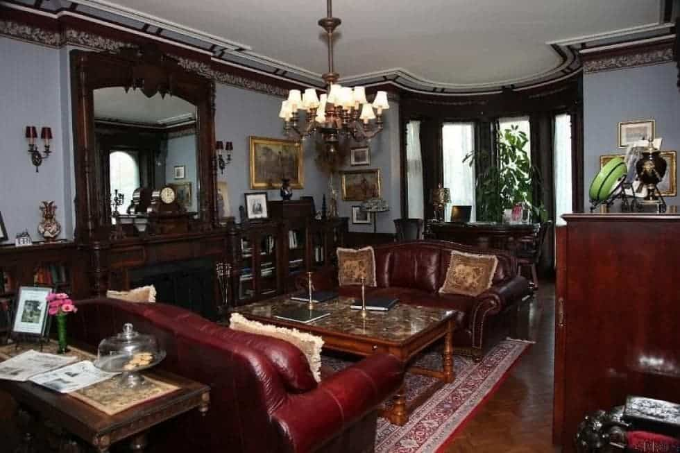 This is the living room that has a couple of dark leather sofas flanking a wooden coffee table that is topped with a chandelier and warmed with a fireplace that has a wooden mantle. Image courtesy of Toptenrealestatedeals.com.