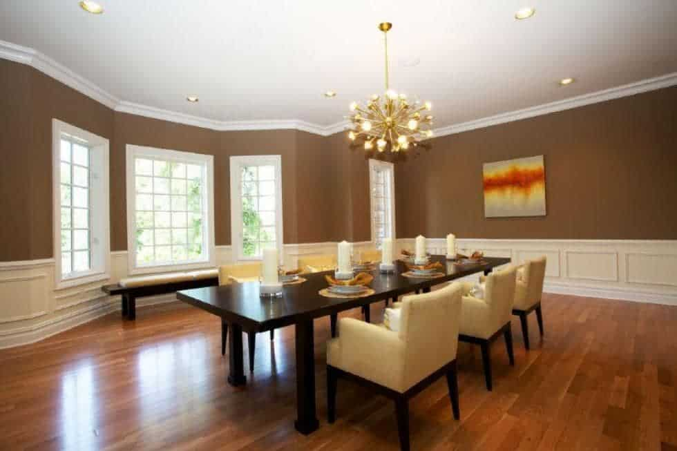 This is the dining room with earthy brown walls above the white wainscoting. This pairs well with the dark table and the golden chandelier. Image courtesy of Toptenrealestatedeals.com.