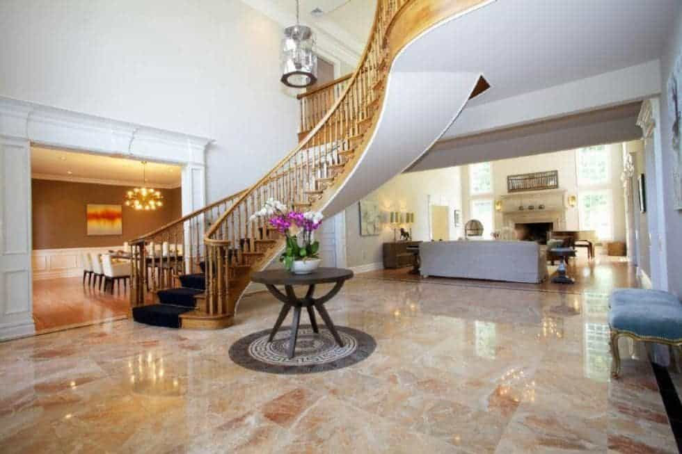 Upon entry of the house, you are welcomed by this foyer with a curved staircase, a round table in the middle of the marble flooring and a pendant light above. Image courtesy of Toptenrealestatedeals.com.