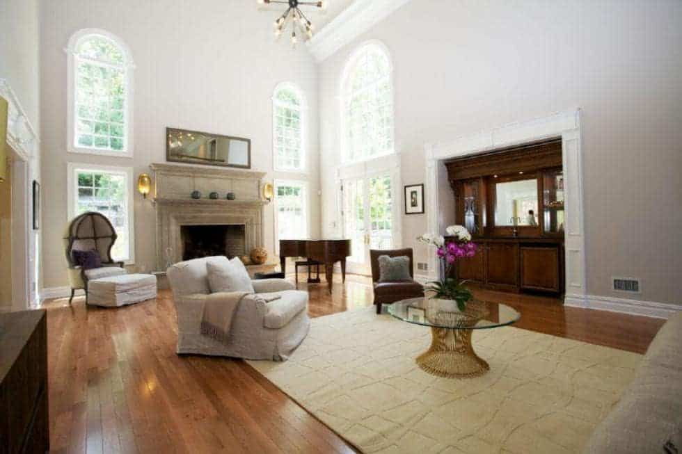 This is the spacious and airy living room with atall bright ceiling complemented by the tall arched windows that bring in natural lighting for the sofas and fireplace. Image courtesy of Toptenrealestatedeals.com.
