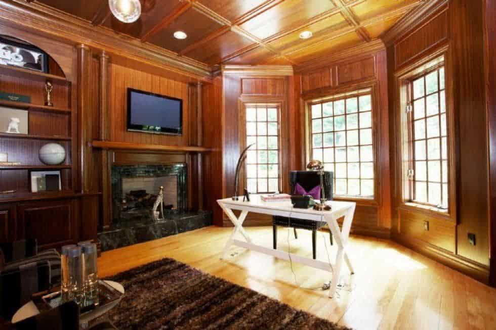 This is the wood-paneled home office with a fireplace on the side. These elements make the white desk stand out. Image courtesy of Toptenrealestatedeals.com.